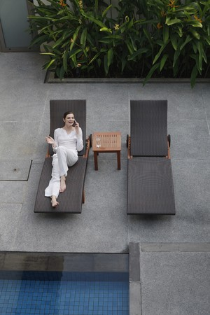 Woman talking on the phone while relaxing on lounge chair photo