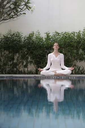 Woman meditating by the pool side Stock Photo - 7644309