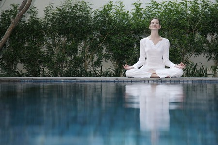 Woman meditating by the pool side Stock Photo - 7644314