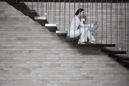 Woman sitting on the stairs using PDA phone photo