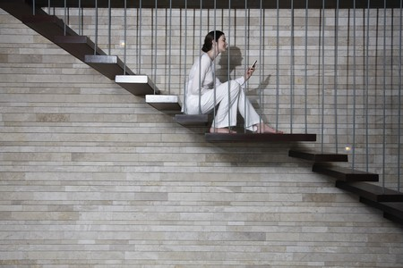 Woman sitting on the stairs and text messaging on the phone photo