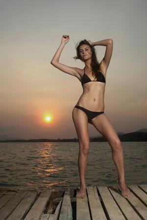 Woman in bikini standing on pier photo