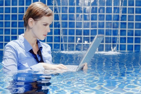 Businesswoman using laptop in swimming pool Stock Photo - 7644411