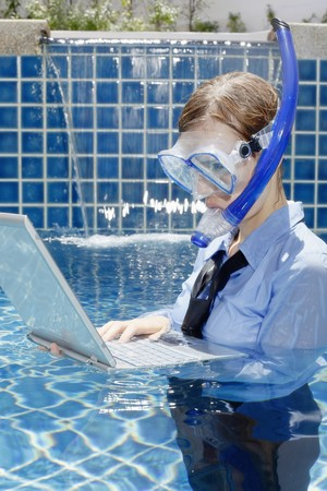 Businesswoman with diving mask using laptop in swimming pool Stock Photo - 7644423