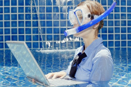Businesswoman with diving mask using laptop in swimming pool photo