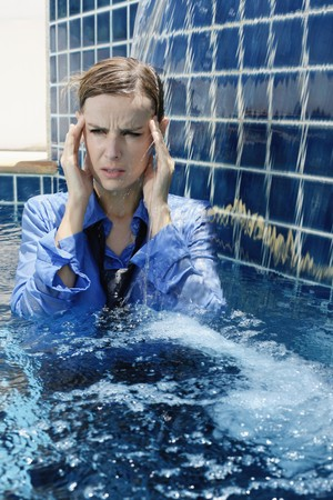 frown: Businesswoman with headache standing in swimming pool