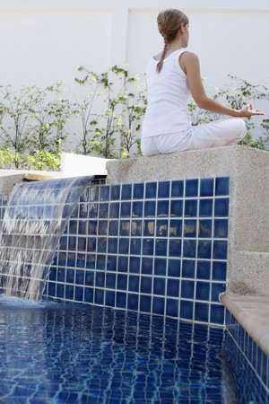 Woman meditating by the pool side Stock Photo - 7644474