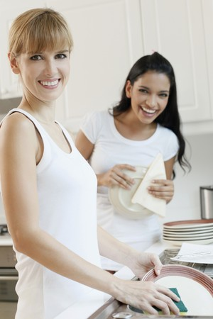 Women washing dishes in the kitchen photo