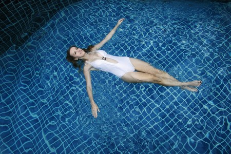 Woman floating in swimming pool photo