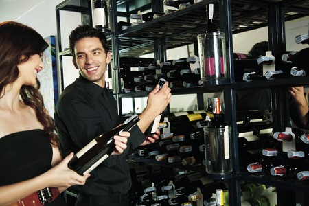 Man and woman selecting wine bottles from rack Stock Photo - 7668428