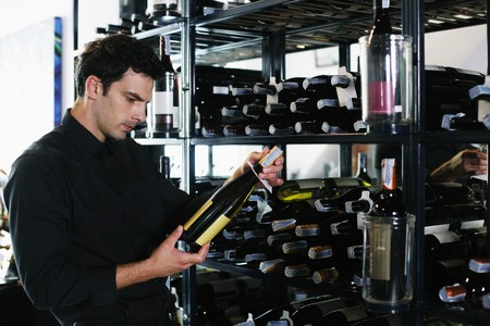 Man selecting wine bottle from rack Stock Photo - 7668395