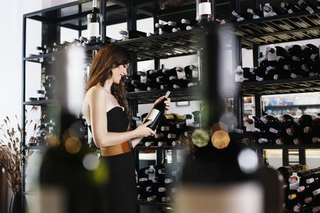 Woman selecting wine bottle from rack photo