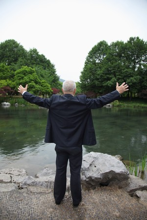 Businessman standing by the lakeside with his arms outstretched photo