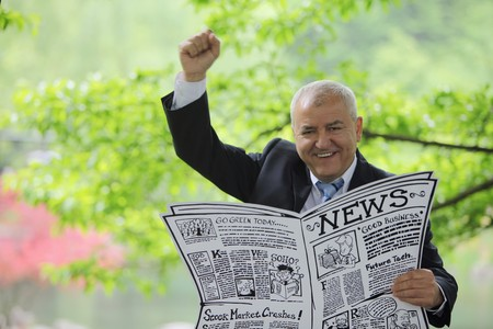 Businessman holding newspaper and raising his hand photo