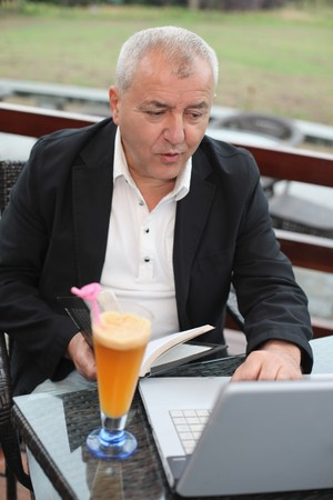 Man holding book and using laptop photo