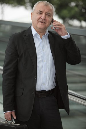 Businessman on escalator, speaking on mobile phone photo