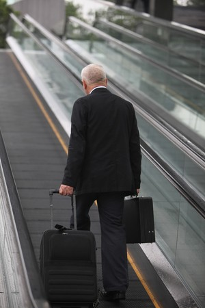 Businessman on escalator, pulling suitcase photo