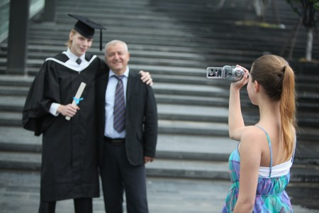 italian ethnicity: Woman filming father and graduate son with a video camera