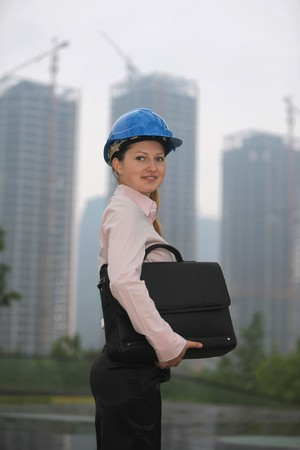 Businesswoman with hardhat carrying bag photo
