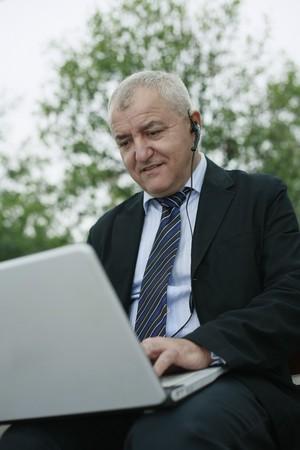 Businessman with telephone headset using laptop photo