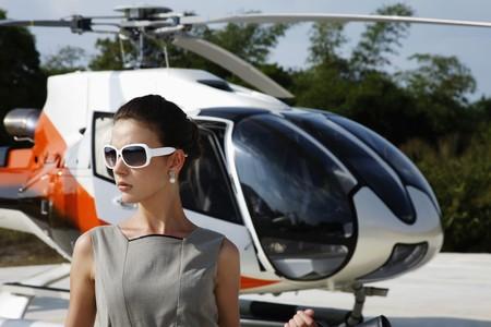 Geschäftsfrau, die Sonnenbrille mit Helikopter im Hintergrund  Standard-Bild