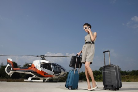 Businesswoman with luggages and briefcase talking on the phone at helipad photo