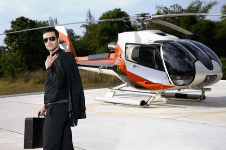 Businessman with briefcase standing at helipad, helicopter in the background photo