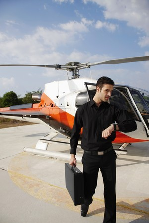 southeastern european descent: Businessman looking at watch while walking from helicopter Stock Photo