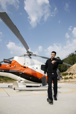 Businessman looking at watch while walking from helicopter photo