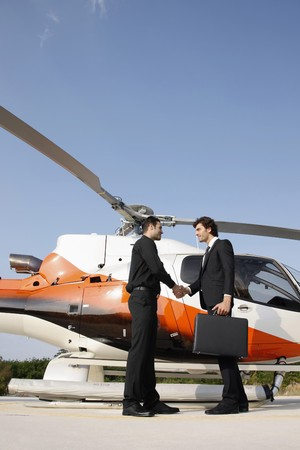 Businessmen shaking hands by helicopter photo