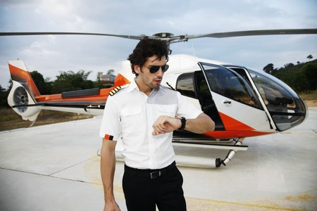 turkish ethnicity: Pilot looking at his watch with helicopter in the background Stock Photo