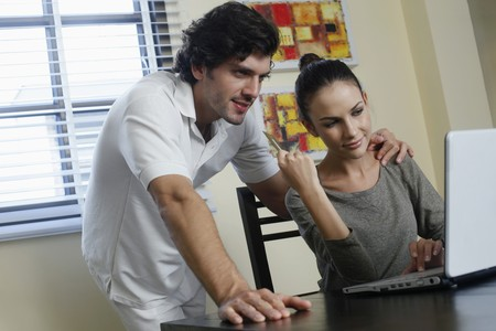 Couple using laptop and credit card for online shopping photo