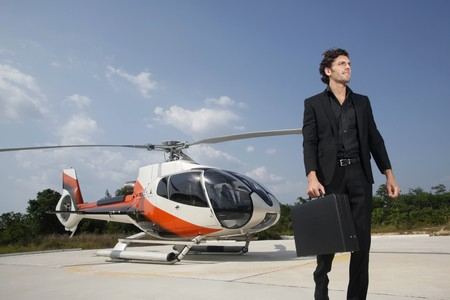 turkish ethnicity: Businessman holding briefcase with helicopter at helipad