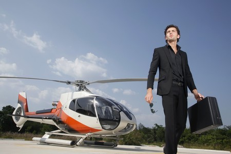 helicopter: Businessman holding briefcase walking away from helicopter Stock Photo