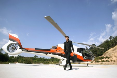 Businessman holding briefcase walking away from helicopter photo