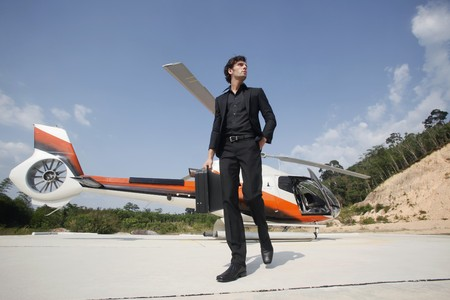 turkish ethnicity: Businessman holding briefcase walking away from helicopter Stock Photo