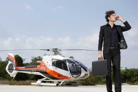 Businessman talking on the phone with helicopter in the background photo