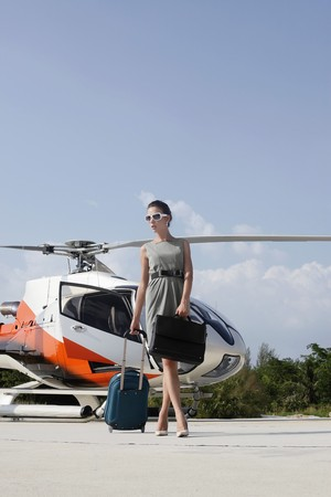Businesswoman with luggage and briefcase walking away from the helicopter photo