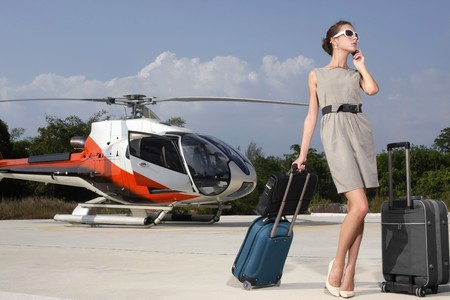 ukrainian ethnicity: Businesswoman with luggage and briefcase at helipad, talking on the phone Stock Photo