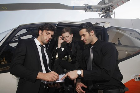 Business people discussing by the helicopter photo