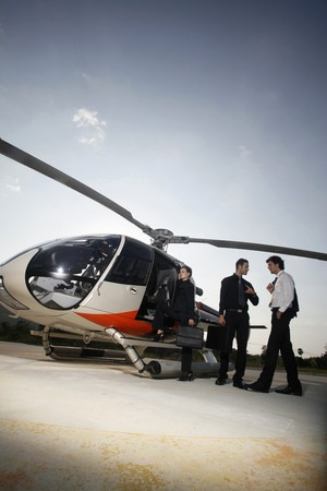 Business people boarding helicopter photo