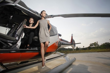 Businesswomen stepping out of helicopter photo