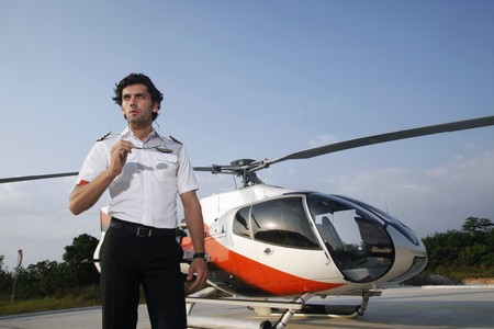 Pilot taking off sunglasses with helicopter in the background