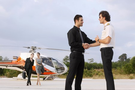 Businessmen shaking hands with pilot while businesswomen are walking away from helicopter Stock Photo - 7685300