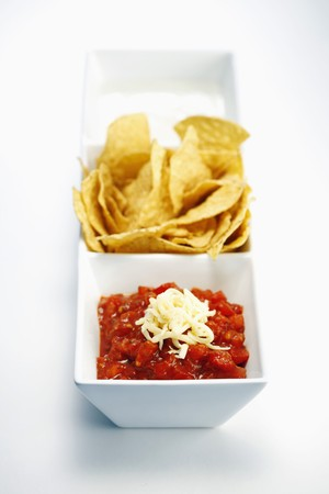 Nachos served with tomato concasse, shredded cheese and sour cream photo