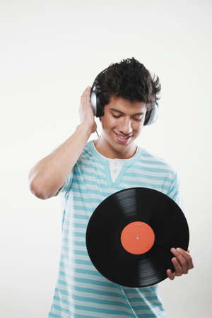 Man listening to music on headphones and holding a vinyl record photo