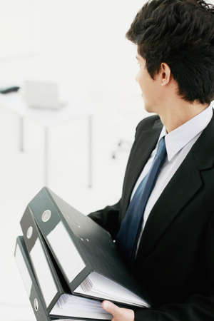 Businessman holding files looking at his desk photo