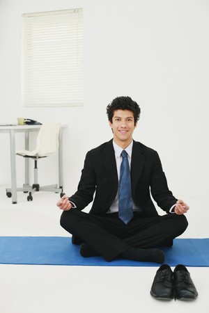Businessman meditating in office photo