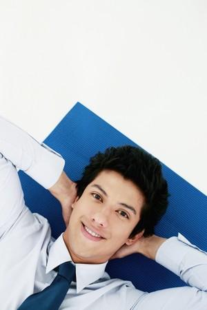 Businessman lying on exercise mat photo