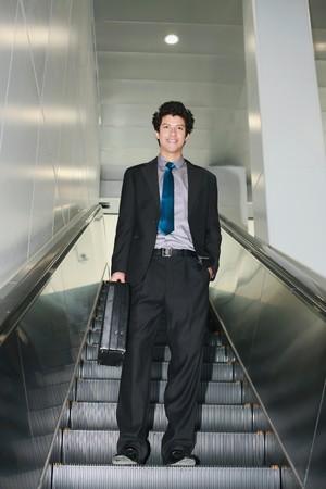 Businessman descending escalator photo